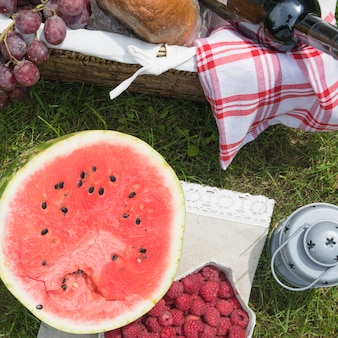 An overhead view of watermelon and raspberries on picnic