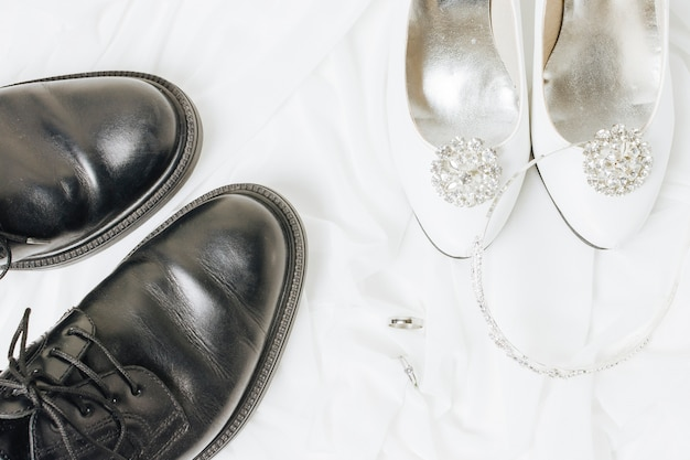 An overhead view of wedding rings; crown and shoes on white cloth