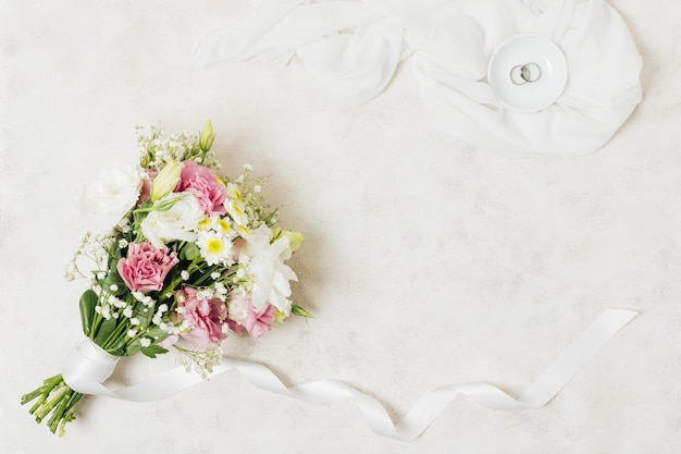 An overhead view of wedding rings on plate over scarf near the flower bouquet