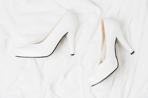 An overhead view of wedding white high heels on white cloth
