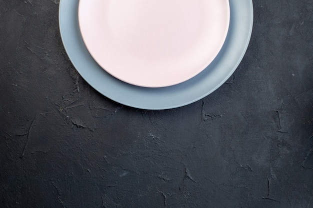 Overhead view of white and blue ceramic empty plates on black background with free space