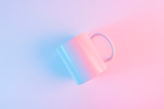 An overhead view of white ceramic mug against pink background