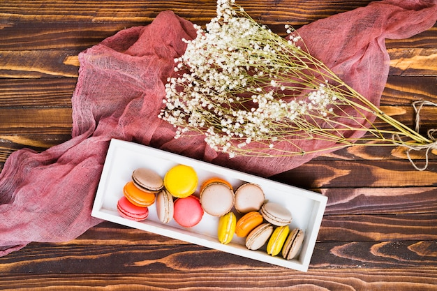 An overhead view of white gypsophila and macaroons in white box over the wooden table