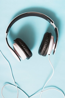 An overhead view of white headphone against blue background
