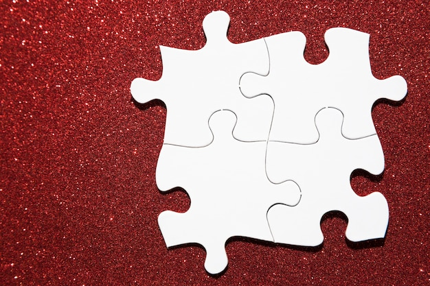 Overhead view of white jigsaw puzzle on red glitter background