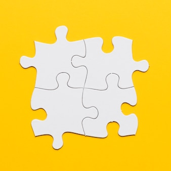 Overhead view of white joint puzzle on yellow background