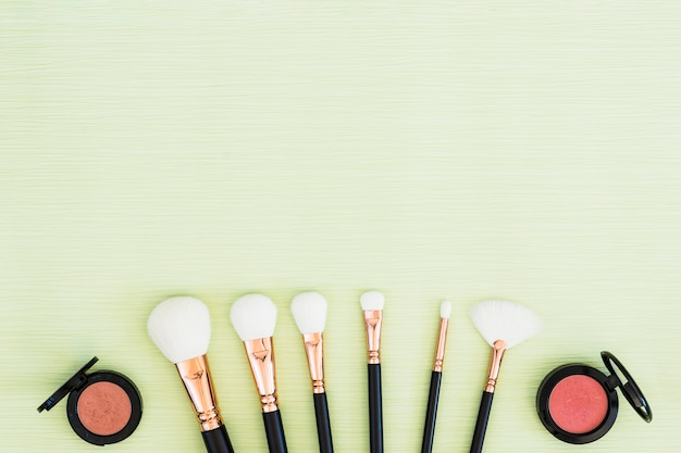 A overhead view of white makeup brushes and pink compact powder on mint green background