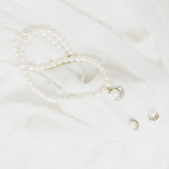 An overhead view of white pearls necklace and earrings on white scarf