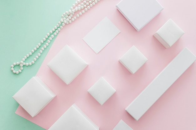 Overhead view of white pearls necklace with different boxes on pastel paper background