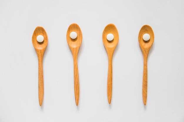 Overhead view of white pill on wooden spoons over the white background