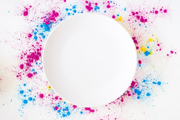 An overhead view of white plate on holi color powder over white background