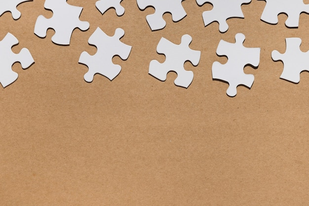 Overhead view of white puzzle pieces on brown paper textured