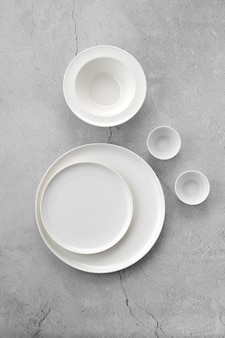 Overhead view of white tableware on grey