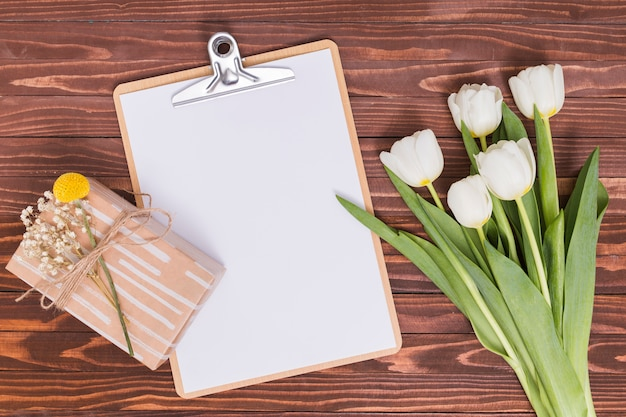 Overhead view of white tulip flowers; blank paper; clipboard and gift box over wooden desk