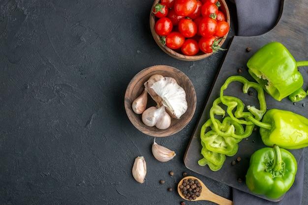 Vista aerea di peperoni verdi tritati interi sul tagliere di legno pomodori nella ciotola garlics sul tovagliolo di colore scuro sul lato sinistro sulla superficie nera