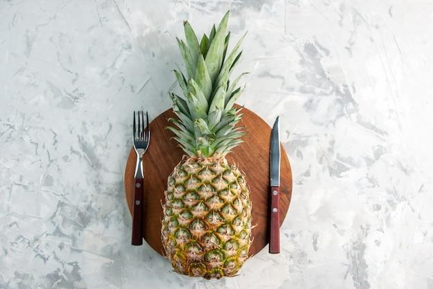 Vista dall'alto dell'intero ananas dorato fresco sul coltello a forchetta del tagliere sulla superficie di marmo