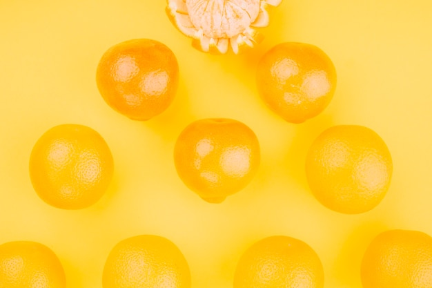 An overhead view of whole oranges on yellow backdrop