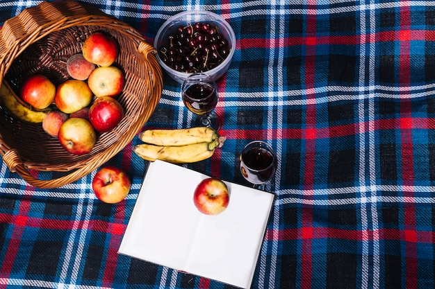 An overhead view of wine glasses; apple; banana and book on blanket