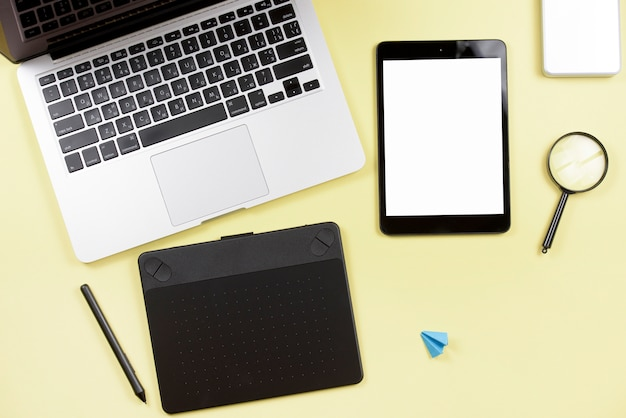 An overhead view of wireless digital tablet; laptop and graphic digital tablet with stylus on yellow background