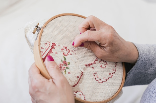 An overhead view of woman embroidering on cross stitching hoop with needles