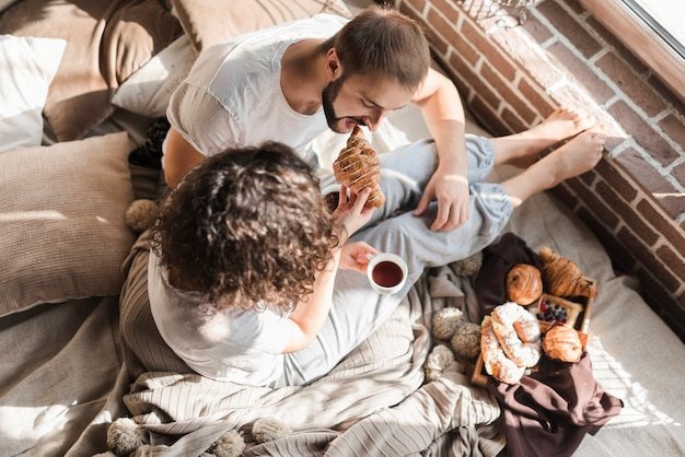 An overhead view of a woman feeding croissant to her husband sitting on bed