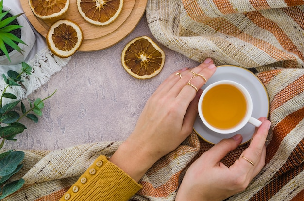 An overhead view of woman's hand holding the herbal tea cup and dried lemon on textured backdrop