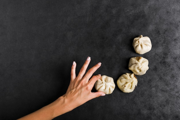 An overhead view of woman's hand holding steam dumplings on black textured background