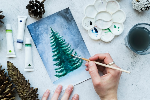 An overhead view of a woman's hand painting christmas tree on canvas