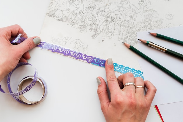 An overhead view of woman's hand sticking the lace on drawing paper