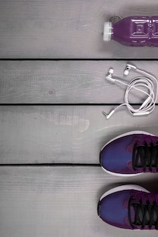 Overhead view woman's workout outfit.  purple running shoes, water bottle