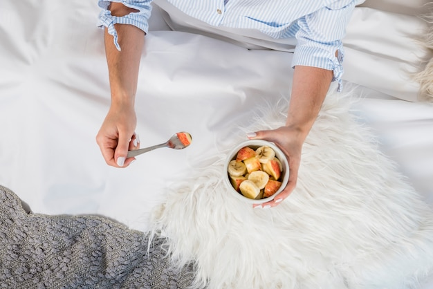 An overhead view of woman sitting in bed holding bowl of fruit salad