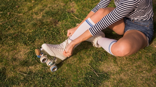 An overhead view of a woman sitting on green grass tying lace on roller skate