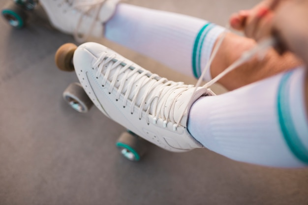 An overhead view of a woman tying roller skate lace