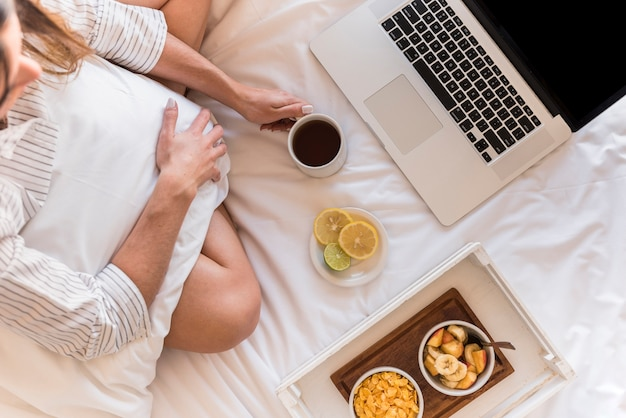 An overhead view of woman with breakfast and laptop on bed