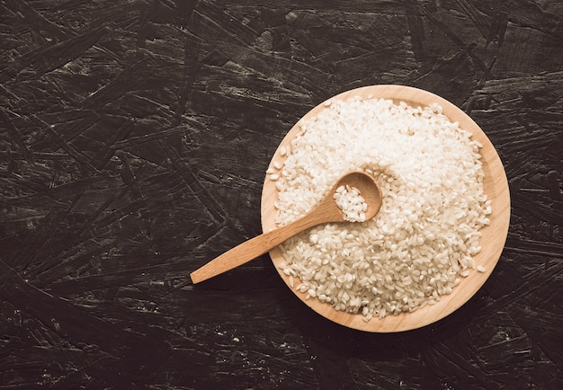 Overhead view of wooden bowl rice grains with spoon