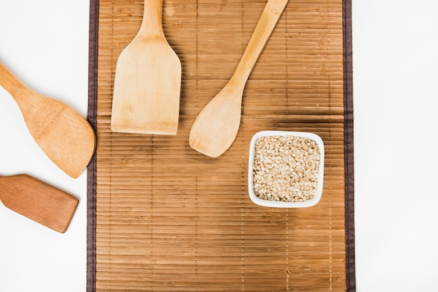 An overhead view of wooden spatulas with uncooked brown rice bowl on placemat