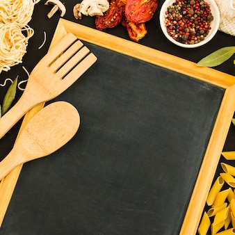 An overhead view of wooden spoon and spatula on blank slate with pasta ingredients