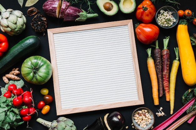 An overhead view of wooden white frame with colorful vegetables on black background