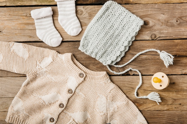 An overhead view of woolen baby's clothing with pacifier on wooden table