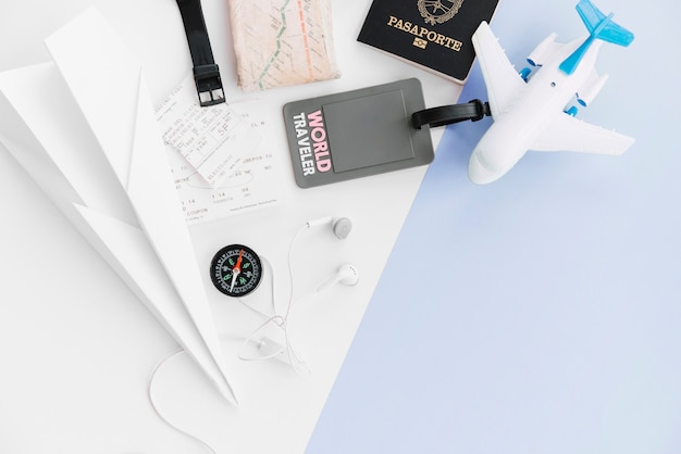 An overhead view of world traveler tag with passport; paper airplane; map; compass; tickets; toy airplane and earphone on dual background