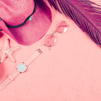 An overhead view of wristwatch; sunglasses; hat; leaf and starfish on pink textured backdrop