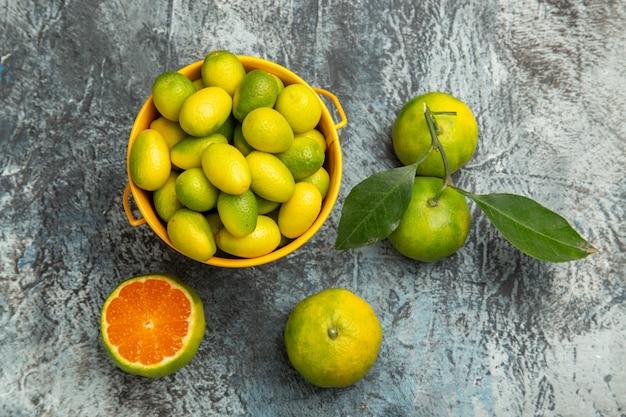 Vista dall'alto di un secchio giallo pieno di mandarini verdi freschi e tagliato a metà mandarini su sfondo grigio