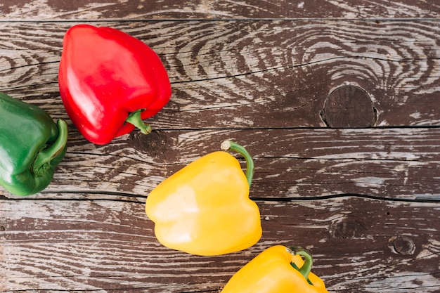 An overhead view of yellow; green and red bell peppers on wooden texture surface