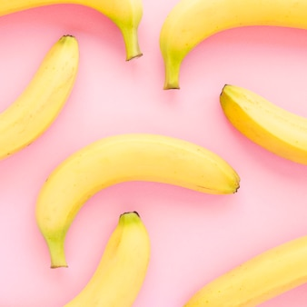An overhead view of yellow organic bananas on pink background