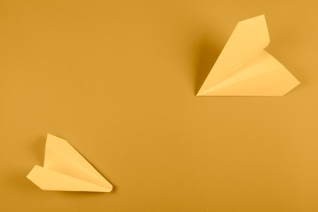 An overhead view of yellow paper airplane on bright colored background