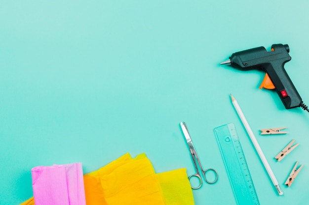 An overhead view of yellow and pink paper; scissor; ruler; pencil; clothespins and electric glue gun on turquoise background