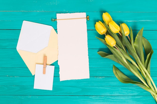 Overhead view of yellow tulip flowers; blank paper; and open envelope above green backdrop