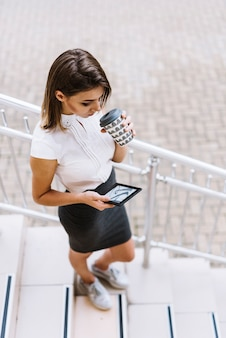 An overhead view of young businesswoman drinking coffee looking at smartphone