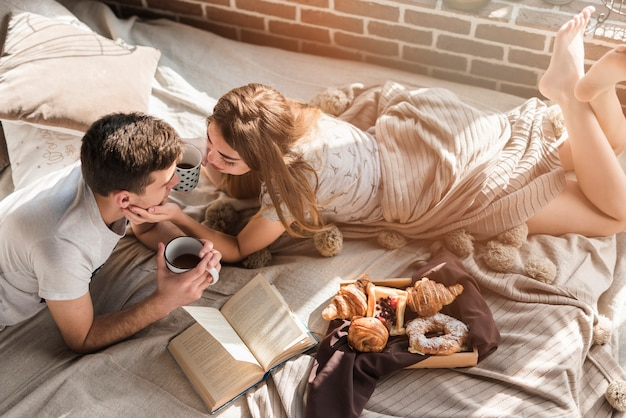 An overhead view of young couple lying on messy bed with breakfast on bed