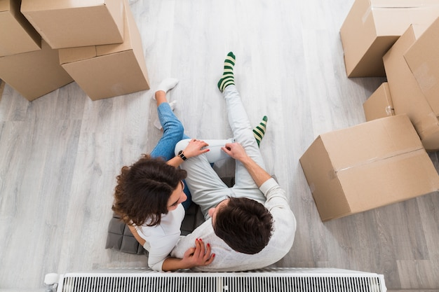 An overhead view of young couple sitting together with moving cardboard boxes at new home